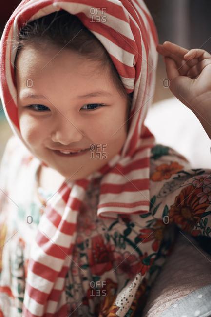 Cute girl wearing blouse on her head like a headscarf