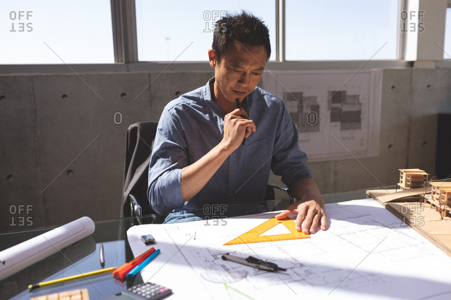 Front view of thoughtful Asian male architect working on blueprint at desk in a modern office.