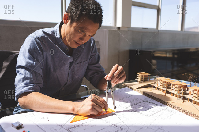 Front view of handsome Asian male architect working on blueprint while using geometry compass and set square at desk in a modern office