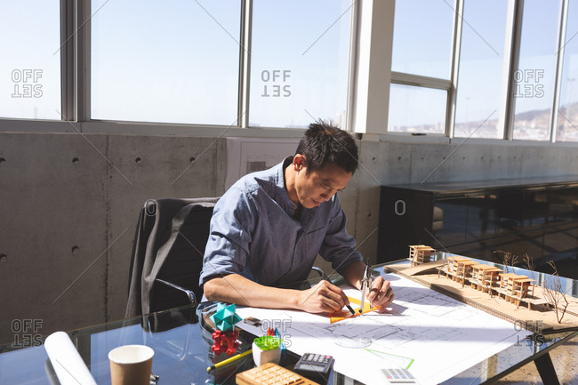 Front view of handsome Asian male architect working on blueprint at desk in a modern office