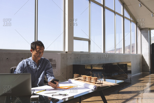 Front view of Asian male architect sitting at desk while using mobile phone and architectural model, triangle ruler, pencils and blueprint on desk in modern office