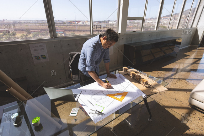 High angle view of a male Asian architect standing at desk and working on a blueprint in a modern office