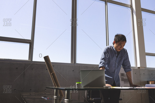Front view of Asian male architect standing at desk and looking blueprint in a modern office