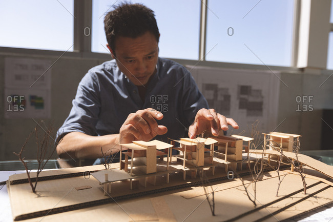 Front view of a male Asian architect working on an architectural building model at desk in a modern office