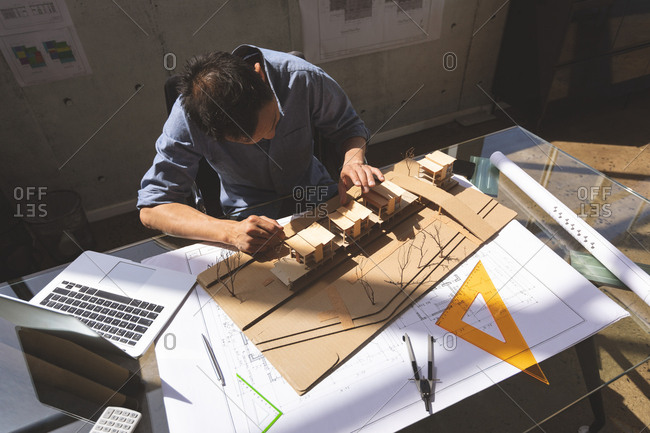 High angle view of male Asian architect working on office building model with his laptop and tools in a modern office