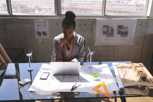 Front view of mixed race businesswoman using laptop at desk in architectural office
