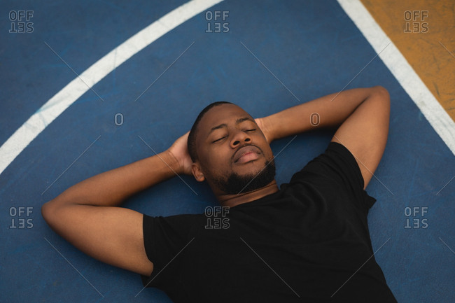 High angle view of young African-American basketball player with hands behind head and eyes closed relaxing on floor in basketball court