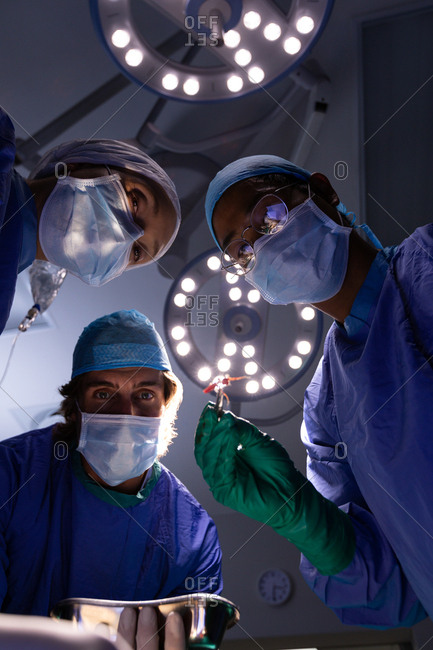 Low angle view of multi-ethnic surgeons concentrated performing operation in operating room at hospital with lights at ceiling