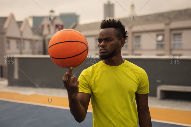 Front view of African-American basketball player balancing ball on finger at basketball court
