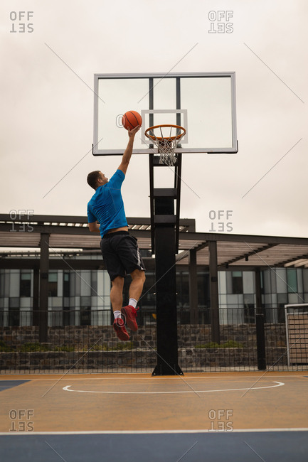 Rear view of basketball player scoring a hoop on a basketball court against a building in background