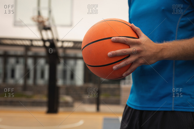 Mid section of basketball player standing with basketball in playground