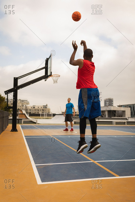 Rear view of African-American basketball player shooting while an other player looking at his shoot on playground