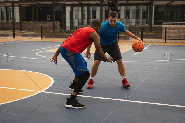 Front view of multi-ethnic players playing basketball at basketball court