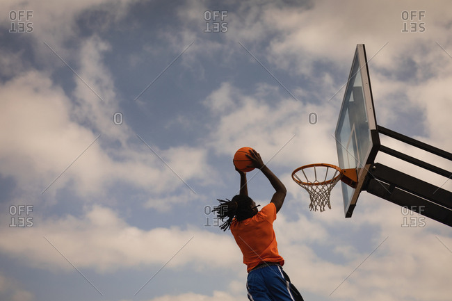 Low angle view of African-American basketball player playing basketball at basketball court while is jumping to score a dunk