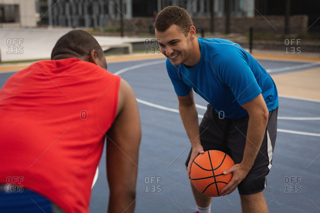 Side view of multi-ethnic basketball players interacting with each other while playing basketball in basketball court