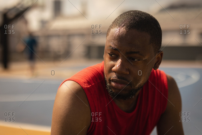Front view of African-American basketball player relaxing at basketball court while he is looking away