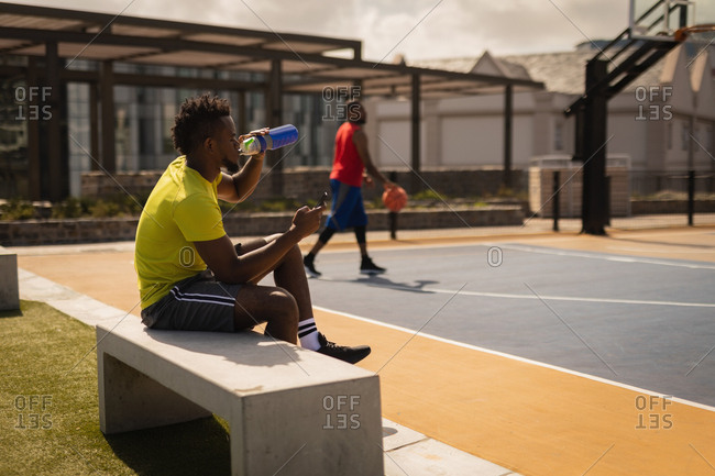 Side view of African-American basketball player drinking water while relaxing at basketball court on a stone bench against another player standing in background