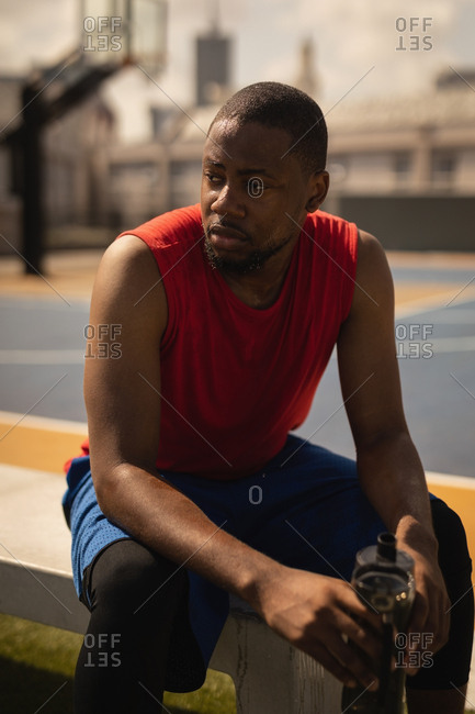 Front view of African-American basketball player in tank top relaxing at basketball court while having a water bottle in his hands