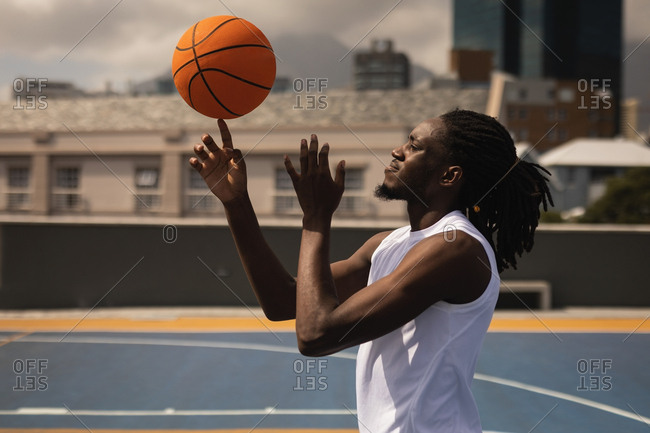 Side view of African-American basketball player balancing ball on finger at basketball court against blur city in background
