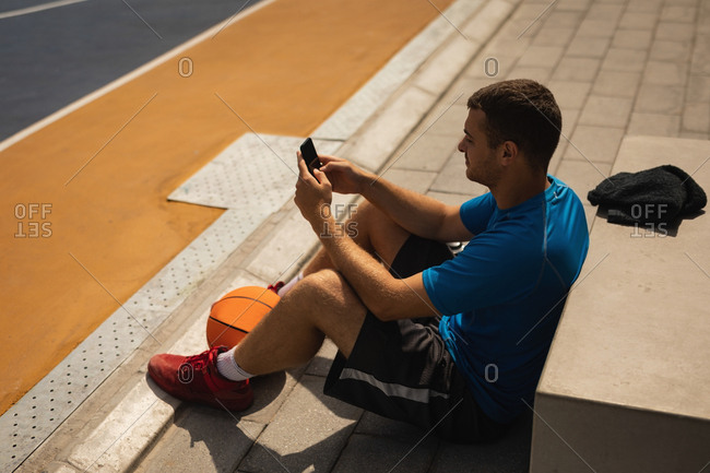 High angle view of young Caucasian basketball player using mobile phone while relaxing on basketball court