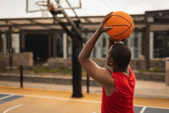 Rear view of African-American basketball player playing basketball on basketball court