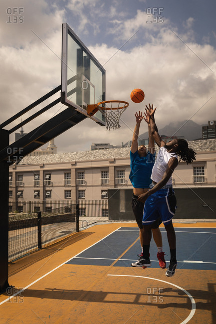 Front view of multi-ethnic basketball players playing basketball at basketball court while they are jumping to score a hoop