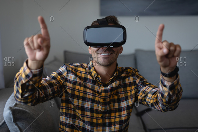 Front view of young Caucasian man using virtual reality headset sitting on the sofa at home