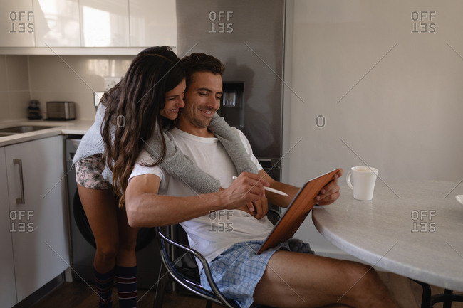 Side view of happy multi-ethnic couple using graphic tablet in kitchen at home