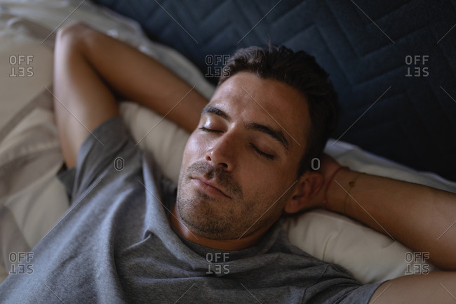 High angle view of young Caucasian man relaxing while lying on bed at home