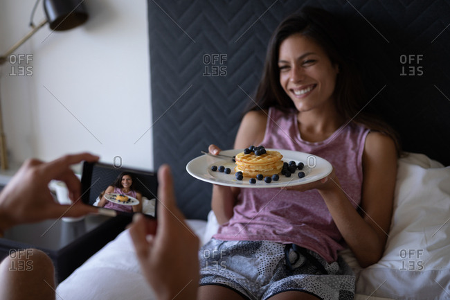 Rear view of Caucasian man taking photo while mixed-race woman holding plate of breakfast in bed at home