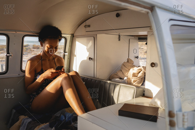 Front view of a beautiful African-American woman using mobile phone in camper van at beach on a sunny day
