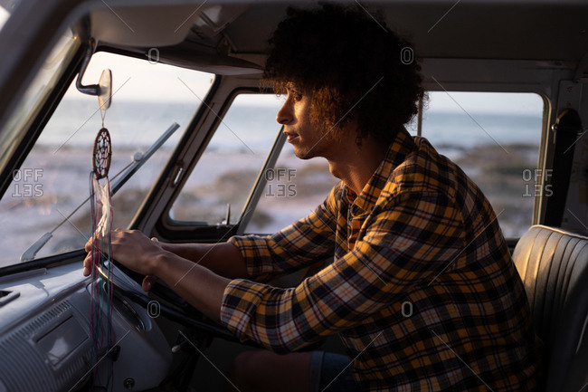 Side view of a Mixed-race man driving a camper van against ocean in background while sundown