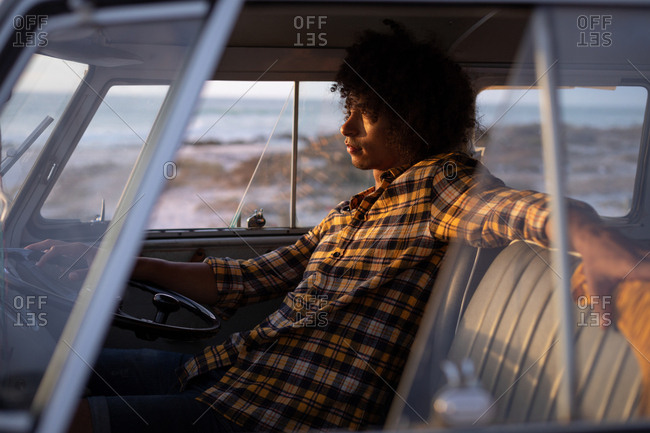 Side view of relaxed Mixed-race man driving a camper van against ocean in background while sundown
