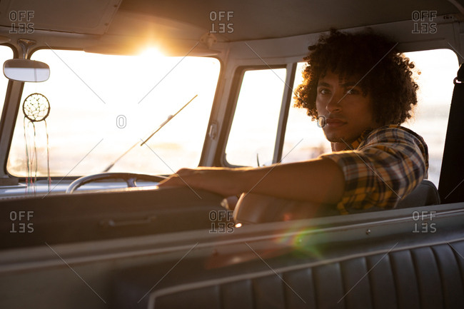 Rear view of a Mixed-race man turning back to looking the camera in a camper van against sundown on beach