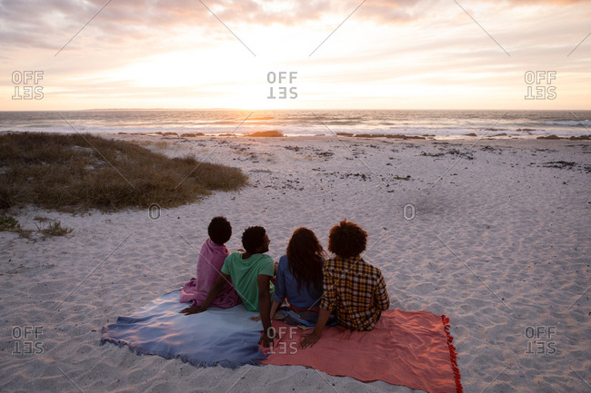 Rear view of multi-ethnic friends group sitting on beach and looking away ocean while sundown