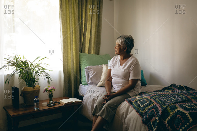 Side view of sad senior mixed race woman sitting on bed at retirement home