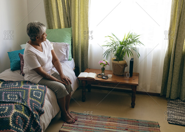 Side view of thoughtful senior mixed race  woman sitting on bed in bedroom at retirement home