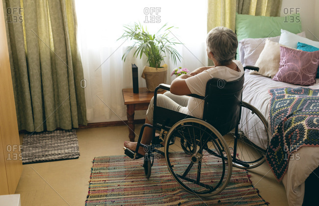 Rear view of thoughtful disabled senior woman siting in wheelchair in bedroom at retirement home