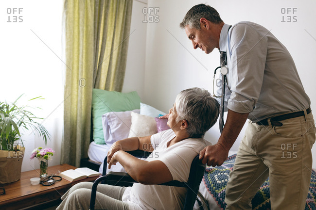 Side view of Caucasian male doctor interacting with senior mixed race female patient at retirement home
