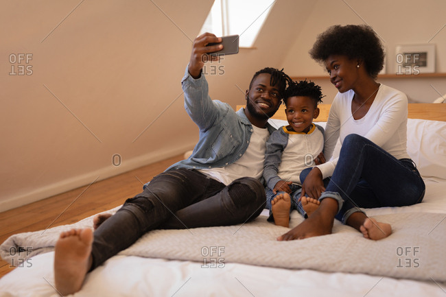 Front view of happy African-American family sitting together and taking selfie at home