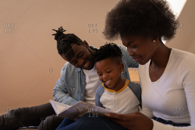 Side view of happy African-American family sitting together and reading storybook at home