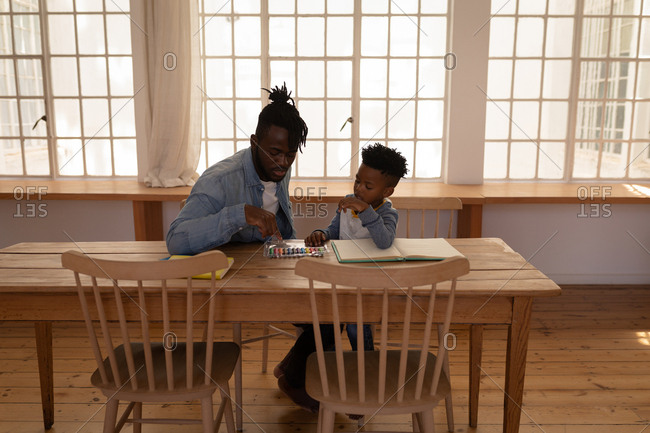 Front view of African-American father assisting his son in drawing while sitting on chair at dining room