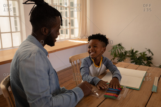 Side view of happy African-American father assisting his son in drawing while sitting on chair at dining room