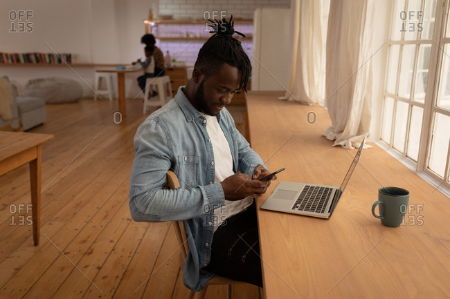Side view of African-American man using mobile phone with laptop on table at home