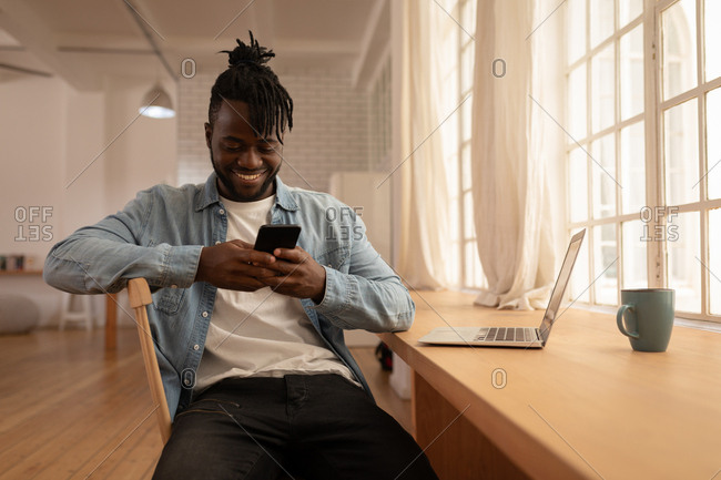 Front view of happy African-American man using mobile phone with laptop on table at home