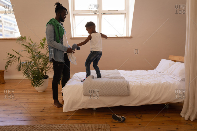 Side view of handsome African-American father undressing naughty son at home