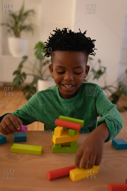 Front view of little cute African-American boy playing with building blocks at home