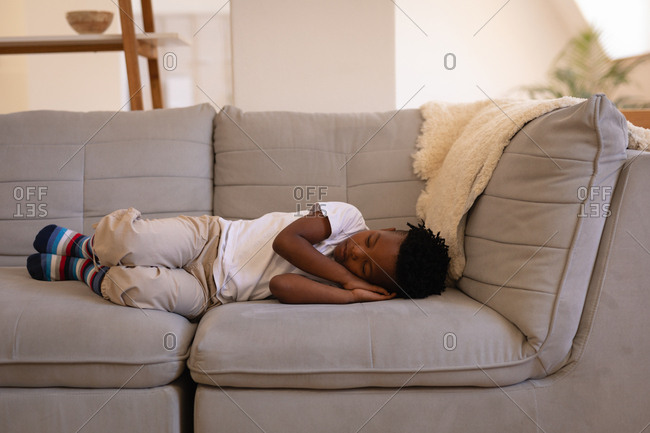 Front view of little cute African-American boy sleeping on sofa at home