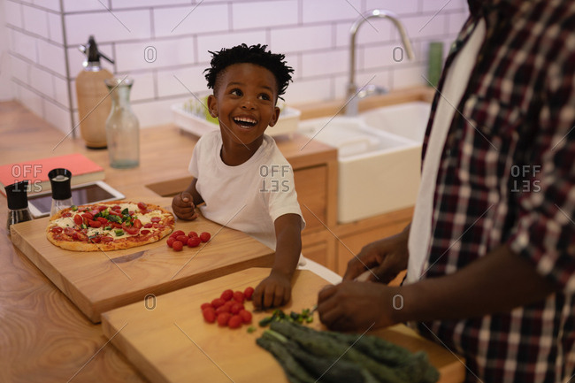 Side view of cute African-American son helping his father in kitchen at home