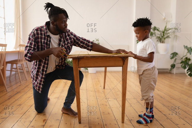 Side view of African-American father and son measuring table with measurement tape
